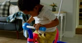 domicílio : Side view of cute little black boy playing in a comfortable home. He is sitting on tricycle 4k