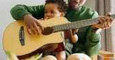 domicílio : Front view of young black father and little son playing guitar in living room of comfortable home. Son sitting on fathers lap 4k Stock Footage