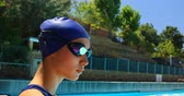 oldal : Female swimmer standing near poolside. Woman looking at camera 4k