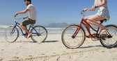 ciclismo : Couple riding bicycle at beach on a sunny day. Calm sea and beautiful sky in the background 4k