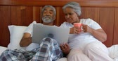 lying on front : Front view of mature couple making video call on digital tablet at home. They are gesturing and drinking coffee 4k