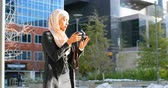 klick : Front view of young Asian woman in hijab clicking photos with digital camera in the city. City life in the background 4k Stock Footage