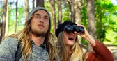 binocolo : Young couple camping in the forest on a sunny day. Woman looking through binoculars in the forest 4k