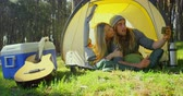 lying on front : Young couple clicking selfie with mobile phone in tent. Couple camping in the forest 4k