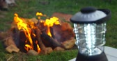kamp ateşi : Close-up of emergency light on table at campsite. Campfire in background at campsite 4k