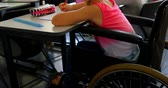 cadeira de rodas : Side view of disabled blonde Caucasian schoolgirl studying at desk in classroom at school. She is writing on notebook 4k