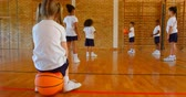 iskoláslány : Rear view of Caucasian schoolgirl sitting on basketball in basketball court at school. Schoolkids practicing basketball in the background 4k