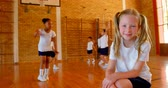 школьница : Low angle view of cute Caucasian schoolgirl relaxing in basketball court at school. Schoolkids practicing basketball in the background 4k