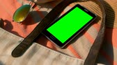 yokluk : Close-up of mobile phone  with green screen and accessories on picnic blanket at beach on a sunny day Stok Video