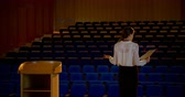 подиум : Rear view of beautiful young Caucasian businesswoman practicing speech in empty auditorium. She is standing on stage 4k