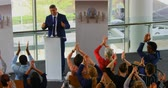 tanácsadás : High angle view of a Caucasian male speaker standing on the podium while being applause by the public in the business seminar 4k
