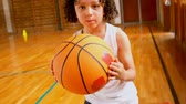 high speed camera : Front view of athletic African American schoolboy standing with basketball in basketball court at school. She is looking at camera 4k