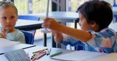 colega : Front view of cute diverse schoolkids studying at desk in the classroom at school. Schoolboy operating wind turbine 4k