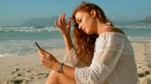 caressing : Side view of young Caucasian woman using mobile phone while sitting and going through her hair with hand on beach in the sunshine 4k Stock Footage