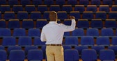 oditoryum : Rear view of senior African American businessman practicing speech in empty auditorium. He is standing and gesturing 4k