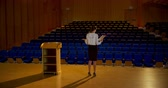 oditoryum : Rear view of beautiful young Caucasian businesswoman practicing speech in empty auditorium. She is standing on stage 4k
