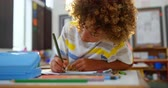 schoolchildren : Front view of African american schoolboy drawing on notebook in the classroom. He is sitting at desk 4k