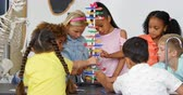 ardósia : Front view of Mixed-race schoolkids studying about dns structure in the classroom. They are looking and touching dna molecule model 4k