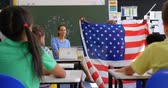 acadêmico : Front view of African american schoolboy explaining about American flag in the classroom. 4k