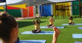 divisa scolastica : Rear view of female teacher teaching schoolkids to perform yoga in the school playground.Schoolkids exercising in the playground 4k