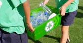 školní vzdělání : Mid section of schoolkids carrying plastic bottles waste  in the school playground. They are studying about bottle recycle 4k Dostupné videozáznamy