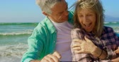 pareja senior : Front view of active senior Caucasian couple taking selfie with mobile phone on the beach.They are embracing each other 4k Archivo de Video