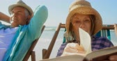 os olhos fechados : Front view of active senior Caucasian woman reading a book on the beach. Senior man relaxing on a sun lounger 4k Vídeos