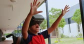 bouche ouverte : Front view of disabled African American schoolboy using virtual reality headset in school corridor. He is gesturing and open his mouth 4k