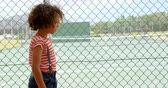 corte : Side view of mixed-race schoolgirl walking near wire mesh fence at school. Tennis court in background 4k Vídeos