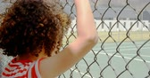 corte : Rear view of mixed-race schoolgirl standing near wire mesh fence at school. She is looking at tennis court 4k Vídeos