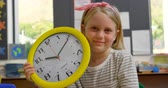 clock : Front view of Caucasian schoolgirl with wall clock sitting at desk in classroom. She is smiling and looking at camera 4k