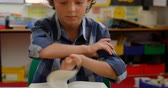 conhecimento : Front view of Caucasian schoolboy studying on desk in classroom at school. He is reading a book 4k