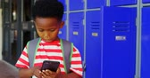 scolaro : Front view of African American schoolboy with schoolbag using mobile phone in school corridor. He is texting text 4k