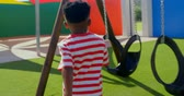 hinta : Rear view of African American schoolboy running towards swing in school playground. He is playing on a sunny day 4k