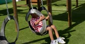 hinta : Side view of African American schoolboy playing on a swing in school playground. He is swinging on swing 4k
