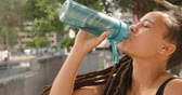 перила : Side view of young African American woman drinking water in the city. She is exhausted and tired 4k