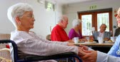 cadeira de rodas : Side view of Caucasian female doctor consoling sad disabled senior woman at nursing home. Senior friend interacting with each other in the background 4k Stock Footage