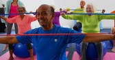retirement home : Front view of Caucasian female trainer training senior people in exercise at fitness studio. They are exercising with resistance band 4k