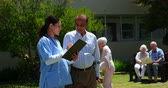 dospělý : Front view of active Asian senior man and female doctor discussing over medical report in the garden of nursing home. They are standing together in the garden 4k