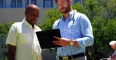 konaklama : Front view of active African American senior man and male doctor discussing over medical report in the garden of nursing home. They are standing together in the garden 4k Stok Video
