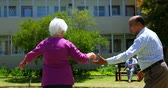 abrigo : Side view of active mixed-race senior couple dancing together in the garden of nursing home. Senior man sitting on a bench in the background 4k Vídeos