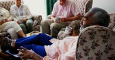 konaklama : Side view of active African american senior man interacting with senior friends in the nursing home. They are drinking coffee 4k