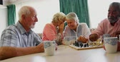 szachy : Active mixed-race senior people playing chess game in the nursing home. Senior women whispering in the background 4k