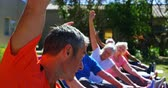 movimento : Side view of Caucasian male trainer training senior people in performing exercise at the garden of nursing home. They are exercising together 4k