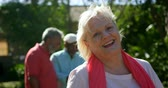 konaklama : Front view of active Caucasian senior woman smiling in the garden of nursing home. She is looking at camera 4k