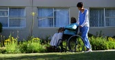 здравоохранение : Side view of Caucasian female doctor pushing senior patient in wheelchair at nursing home. They are walking in the garden 4k Стоковые видеозаписи