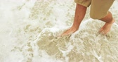 週末 : Low section of man walking barefoot on the beach. Sea surf in the background 4k