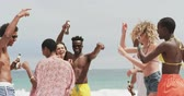socialisation : Group of mixed-race friends dancing together on the beach. They are having fun 4k
