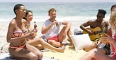 socialisation : Group of mixed-race friends interacting with each other on the beach. They are drinking beer 4k