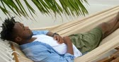длина : High angle view of African american man sleeping in a hammock at beach. He is asleep 4k